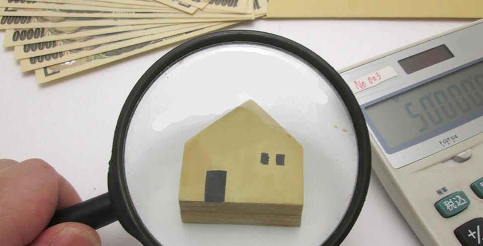 虫眼鏡で積木の家を見る