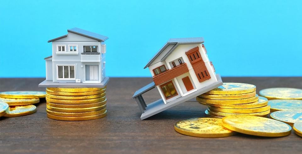 コインの地盤にに積まれた家と崩れた家
